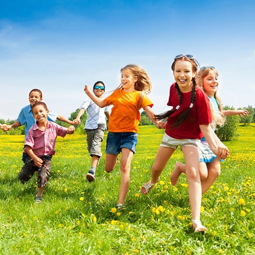 School aged children running through a green grassy field